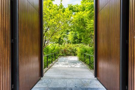 door opening: Large wooden door opening to green outside