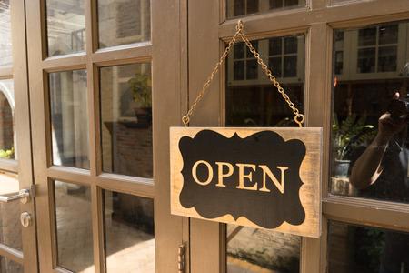 ventanas abiertas: Muestra de la tarjeta de madera que dice Abierto de un restaurante