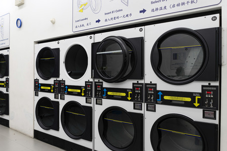 oversize load: Singapore - September 8th, 2015: Coin operated laundromat washing and drying machine in China town housing.