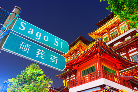 Street sign on Sago Street with Budda Tooth Relic Temple background Редакционное