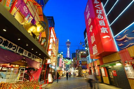 city fish market sign: OSAKA, JAPAN - 26 APRIL 2016: Unitentified tourists on Shinsekai street. Also visible is Tsutenkaku tower.