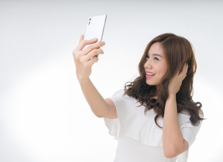 Young attractive asian female taking selfie, on white Stock Photo