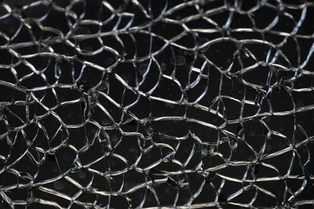 Damaged glass window fracture texture, close up