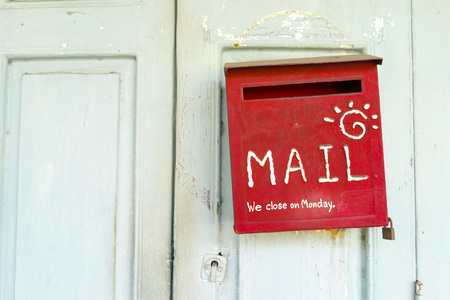 Red mail box on a wooden door