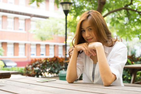 Pretty asian woman smiling sitting behind table