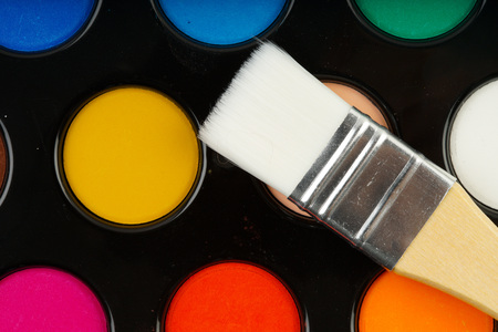 Colorful water color palette and a brush on black Stock Photo