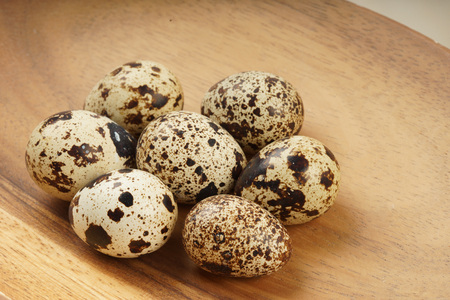 Quail egg group on brown wooden bowl