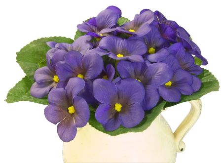 violets: Bouquet of artificial violets in an old jug on a white background Stock Photo