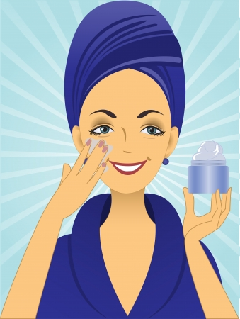 woman face cream: beautiful young woman in blue bathrobe puts on the face cream