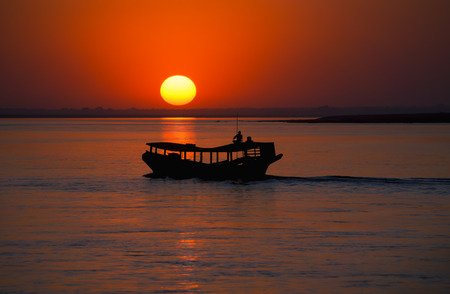 big ball: Sunset with a big ball in red at the Irrawaddy in Myanmar