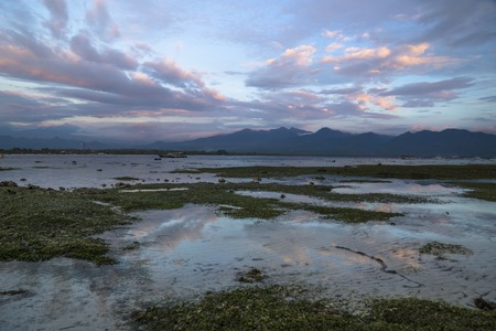 VIew to Lombok mountains from the beach of Gili Air during sunset with purple cloudscape, Indonesia