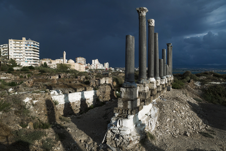 Pillars with cityscape in sunlight during storm in ruins with blue dramatic cloudscape in Tyre, Sour, Lebanon