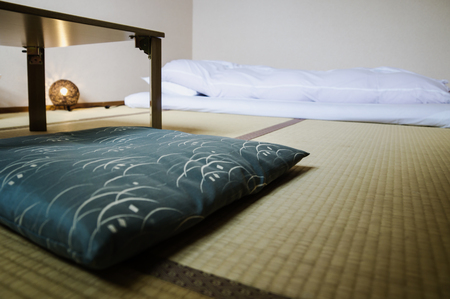 Traditional Japanese Ryokan room with tatimi mats and futon, pillow and table, Japan