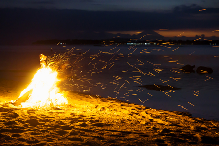 Flying sparks from bonfire at the beach of Gili Air with volcano Agung of Bali during sunset in the background