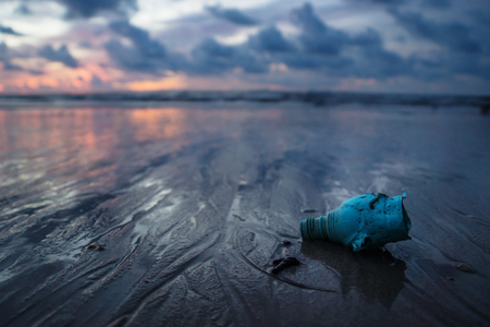 Plastic bottle, garbish and trash littering the ocean at the beach during sunset, Koh Lanta, Thailand