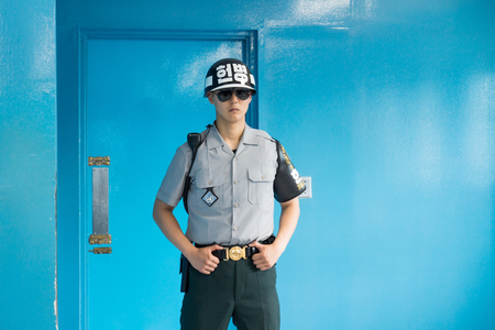 JSA within DMZ, Korea - September 8 2017: UN soldier with typical UN helmet in blue building at North South Korean border guarding the door to North Korea at Korean Demilitarized Zone, Panmunjom Editorial
