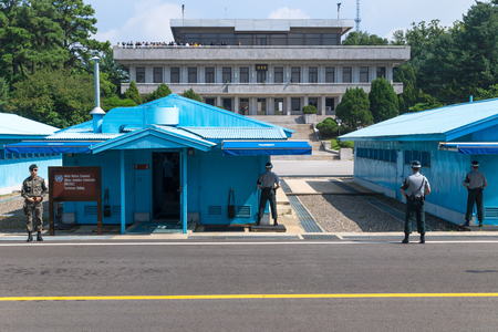 JSA within DMZ, Korea - September 8 2017: UN soldiers close in front of blue buildings at North South Korean border with North Korean tourists on the balcony in the background at Korean Demilitarized Zone, Panmunjom
