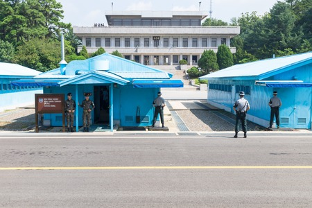 JSA within DMZ, Korea - September 8 2017: UN soldiers and 2 soldiers with camouflage clothes in front of blue buildings at North South Korean border with North Korean tourists in the background on the balcony at Korean Demilitarized Zone, Panmunjom