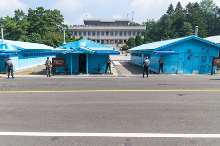 JSA within DMZ, Korea - September 8 2017: 5 UN soldiers and one normal soldier in front of blue buildings at North South Korean border with North Korean tourists on the balcony in the background at Korean Demilitarized Zone, Panmunjom Editorial