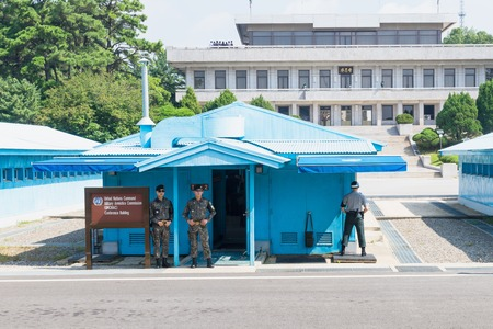 JSA within DMZ, Korea - September 8 2017: UN soldiers and soldiers in camoulage clothes in front of blue buildings at North South Korean border with North Korean tourists in the background making pictures at Korean Demilitarized Zone, Panmunjom