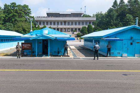 JSA within DMZ, Korea - September 8 2017: UN soldiers and soldiers in front of blue buildings at North South Korean border with North Korean tourists in the background at Korean Demilitarized Zone, Panmunjom