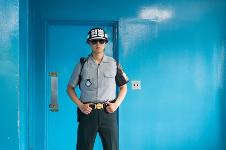 JSA within DMZ, Korea - September 8 2017: UN soldier in blue building at North South Korean border view from the front guarding the door to North Korea at Korean Demilitarized Zone, Panmunjom