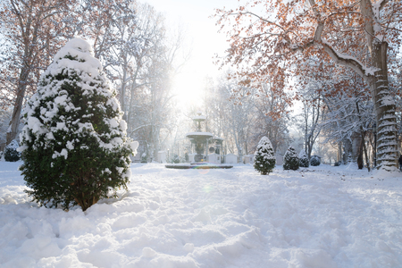 Fountain of Zrinjevac Park in Zagreb in winter with snow and sunshine and s light beam, Croatia, Europe
