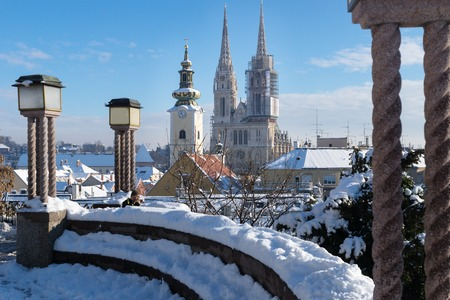 seating area: View over Zagreb during winter with snow with view to towers of church and cathedral and seating area with laternsat a sunny day, Zagreb, Croatia, Europe