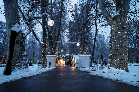 Zagreb, Croatia: January 6 2016: Advent market with foodstalls in the night with christmas decoration lights with snow in Zrinjevac Park in Zagreb in winter Stock Photo - 89899559