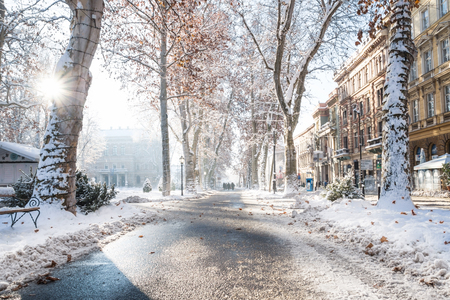 Zagreb, Croatia: January 7 2016: Footpath with decorated trees, sunbeam and walkers in Zrinjevac Park in Zagreb in winter with snow and sunny weather