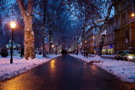 Zagreb, Croatia: January 6 2016: Footpath with decorated lightening trees and walkers in Zrinjevac Park in Zagreb at night in winter with snow