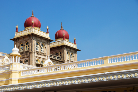 Towers of Mysore Palace with red domes on blue sky, Mysore, India