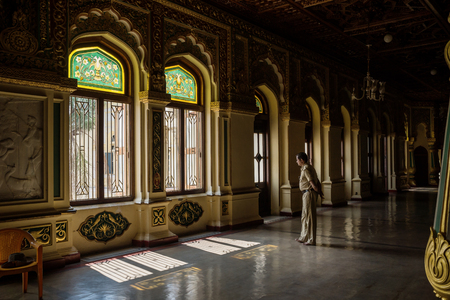 Mysore, India - December 10 2017: Decorated windows with golden pillars of Mysore Palace with shadows and security man