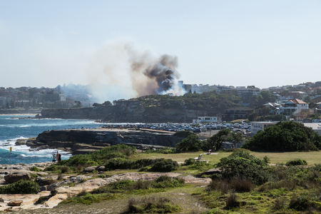 Sydney, Australia - 17 February 2018: Bushfire with dark smoke at Dunningham Reserve between Coogee Beach and Gordons Bay Editorial
