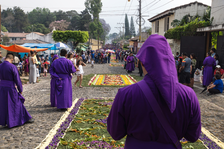 Antigua, Guatemala: March 18 2018: Purple robed man looking at the procession of San Bartolome de Becerra in 1a Avenida with streets full of incense smoke with visitors Publikacyjne