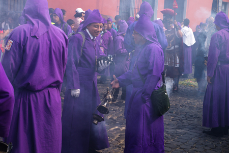 Antigua, Guatemala: March 18 2018: Two young purple robed men in incense smoke at the procession of San Bartolome de Becerra in 1a Avenida