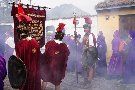 Antigua, Guatemala: March 18 2018: Man with roman soldier smiling at the procession of San Bartolome de Becerra in 1a Avenida, full of incense smoke