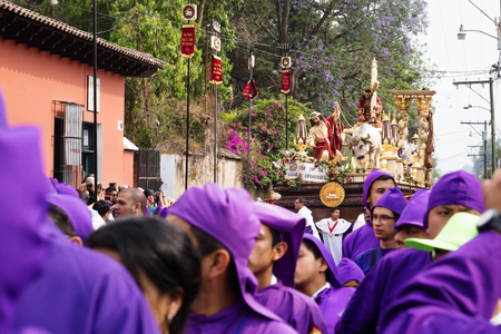 Antigua, Guatemala: March 18 2018: Altar boy in front of a float with Christ and a cross at the procession of San Bartolome de Becerra in 1a Avenida Editorial