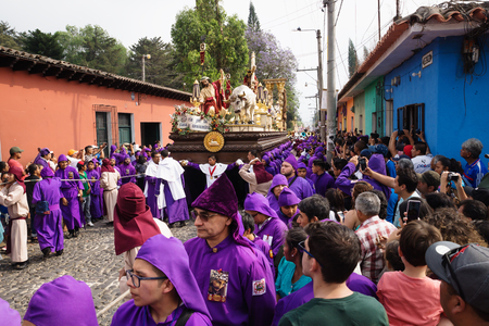 Antigua, Guatemala: March 18 2018: Visitors watching purple robed men carrying a float with Christ and a cross at the procession of San Bartolome de Becerra in 1a Avenida