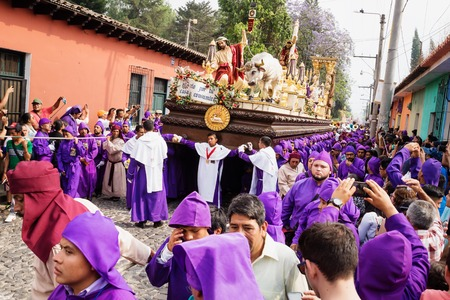 Antigua, Guatemala: March 18 2018: Purple robed men carrying a float with Christ and a cross at the procession of San Bartolome de Becerra in 1a Avenida Editorial