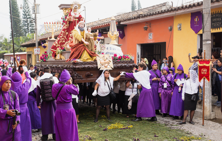 Antigua, Guatemala: March 18 2018: Woman in front of a float with Mary, John and Jesus on top at the procession of San Bartolome de Becerra in 1a Avenida Editorial