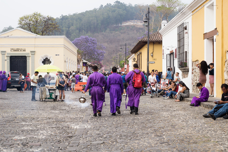 Antigua, Guatemala: March 18 2018: Three purple robbed men with incense smoker on the cobbled streets for the procession San Bartolome de Becerra at 3a Avenida Norte Editorial
