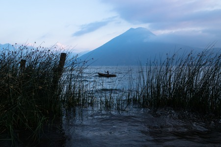 Fisherman between the grass during sunset at Lake Atitlan with volcanoes in the background at the shore of San Marcos, Guatemala