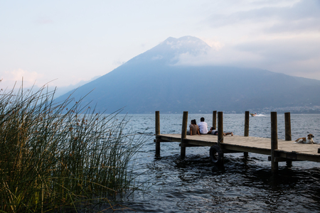 San Marcos, Lake Atitlan, Guatemala - March 30 2018: three tourists and a dog sitting on the pier for watching sunset with volcano San Pedro in the background