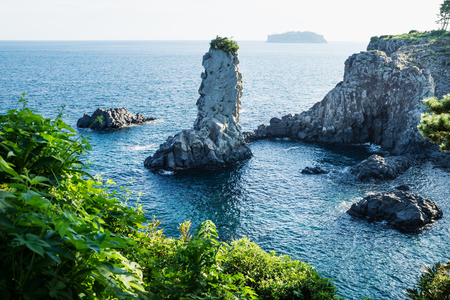 Rock formation Oedolgae in dark blue ocean with green efeu at the cliffs at Seogwipo, Jeju Island, Korea Stock Photo