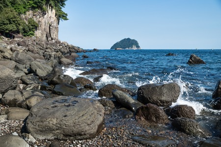 Black volcanic stones with a watersplash with view on Menseom Island along the coastline of Seogwipo, Jeju Island, South Korea Stockfoto