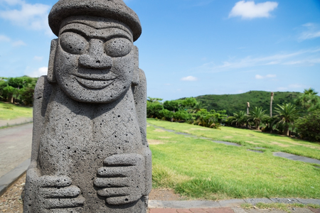 Dol Harubang statue in green grassland and trees in background at Yongmeori Beach, Sanbang-ro, Jeju Island, South Korea