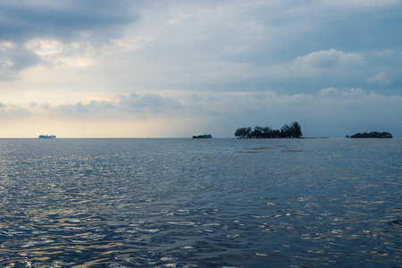 Flat small islands in front of Utila with dramatic cloudscape, Honduras, Central America Stock Photo