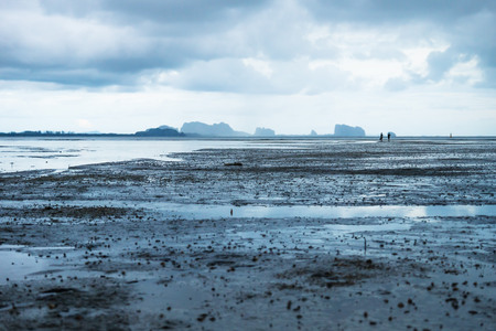 Couple walking in low tide in ocean with carst mountains in background and cloudscape at Koh Mook, Thailand, Asia