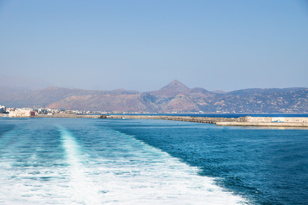 Leaving Heraklion by ferry with view to mountains and port of Crete with trail of the ferry, Heraklion, Greece, Europe